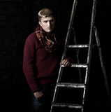 Elegant man in a sweater, jeans and a scarf Royalty Free Stock Images