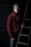 Elegant man in a sweater, jeans and a scarf Stock Photography