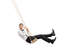 Elegant man swinging on a wooden swing. Elegant man with a black bow-tie and suspenders swinging on a wooden swing isolated on white background Royalty Free Stock Photos
