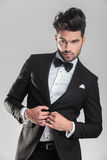 Elegant man in tuxedo closing his jacket Royalty Free Stock Image