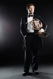 Elegant man in tuxedo with french horn Stock Image