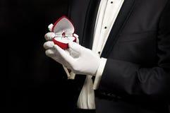 Elegant man in tuxedo holding engagement ring Royalty Free Stock Photography