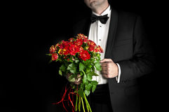 Elegant man in tuxedo holding red roses. Isolated on black Stock Images