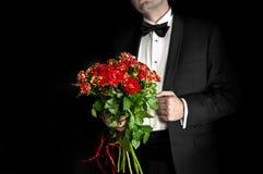 Elegant man in tuxedo holding red roses Stock Images