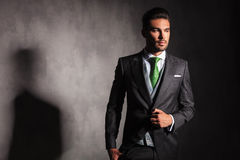 Elegant man in tuxedo jacket buttoning his coat looks away Royalty Free Stock Images