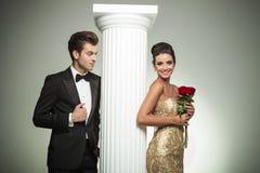 Elegant man in tuxedo looking at his laughing woman Stock Image