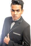 Elegant man in tuxedo unbuttoning his coat Stock Image