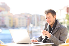 Elegant man using a laptop in a coffee shop Royalty Free Stock Photos