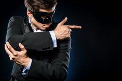 Elegant man. Wearing black mask and suit posing indoors royalty free stock photography