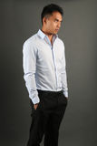 Elegant man wearing a blue shirt and a black pants posing. Over a gray background Royalty Free Stock Photo