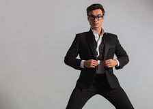 Elegant man wearing glasses unbuttoning his tuxedo. And looks at the camera on grey background Royalty Free Stock Photos