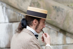 Elegant man wearing old fashioned hat and pipe. STOCKHOLM - SEPT 19, 2015: Elegant man wearing old fashioned trilby hat smoking a pipe in the Bike in Tweed event Royalty Free Stock Image