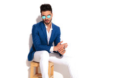Elegant man wearing sunglasses sitting on chair and rubbing  pal Royalty Free Stock Photography