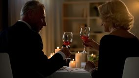 Elegant man and woman holding red wine glasses, senior couple on date, love royalty free stock images