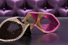 Elegant mask for Masquerade. In front of a button tufted purple silk background stock photos