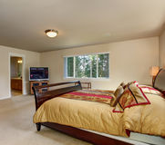 Elegant master bedroom with wooden bed frame. Royalty Free Stock Images