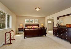 Elegant master bedroom with wooden bed frame. Royalty Free Stock Photography