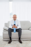 Elegant mature businessman text messaging at home Royalty Free Stock Image
