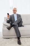 Elegant mature businessman text messaging at home Stock Photography