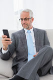 Elegant mature businessman text messaging on sofa Royalty Free Stock Images