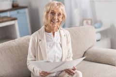 Elegant mature businesswoman checking business plan. Business documentation. Gorgeous beautiful mature businesswoman looking at camera while holding papers and Royalty Free Stock Images