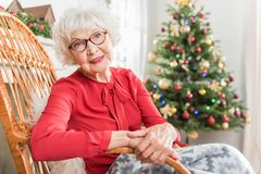 Elegant mature lady is expressing gladness about celebration. Great mood. Portrait of charming elderly woman is sitting in rocking chair and looking at camera royalty free stock images