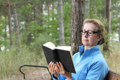 Elegant mature woman with blond hair and glasses reading a book outside in the park with copy space Royalty Free Stock Photography