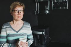 Elegant mature woman drinking coffee in the kitchen. Coffee machine, dark interior Stock Photography