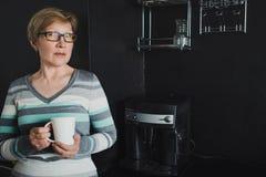 Elegant mature woman drinking coffee in the kitchen. Coffee machine, dark interior Stock Photos