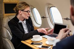 Elegant mature woman working with colleague. Good looking lady in formal clothes discussing work matters with her companion while sitting in airplane seat. She stock image
