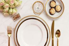 Elegant meal time. Modern styled dinner table with elegant white and gold serving ware, and dessert. Copy space Royalty Free Stock Image