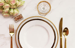 Elegant meal time. Modern styled dinner table with elegant white and gold serving ware, and roses. Copy space Royalty Free Stock Image
