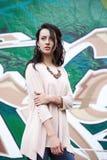 Elegant meisje op graffitiachtergrond stock afbeeldingen