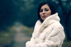 Elegant meisje in witte laag met hoge kraag Stock Foto