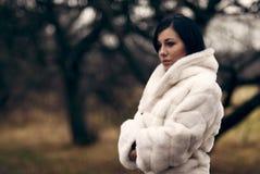 Elegant meisje in witte laag met hoge kraag Royalty-vrije Stock Afbeeldingen