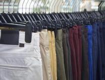 Elegant men clothing in a store, lots of pants  elegant formal wear, gentleman style , autumn spring Wedding clothes. Elegant men clothing in a store, lots of stock images