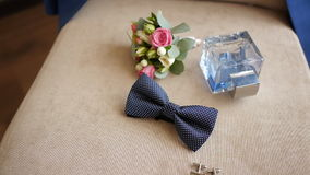 Elegant men's accessory for wedding, toilet water with buttonhole lie on a chair, his jacket hanging on the back of a stock footage