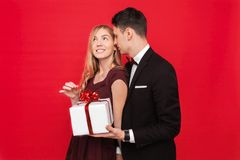 An elegant man in a suit gives a surprise to a woman, gives her a gift, on a red background, the concept of women`s day royalty free stock image