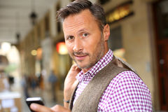Elegant middel-aged standing in street. Man in shopping street using mobile phone Stock Image