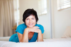 Elegant middle aged woman. Lying on bed relaxing Royalty Free Stock Photos