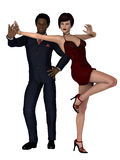 Elegant mixed race couple. Man of African ethnicity in smart blue suit with woman in red silk dress and  ruby jewellery standing one legged Royalty Free Stock Images