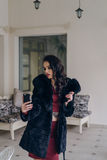 Elegant model in black coat with phone. Portrait of a seductive lady in an elegant coat royalty free stock photos
