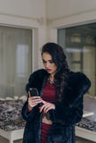 Elegant model in black coat with phone. Portrait of a seductive lady in an elegant coat royalty free stock image