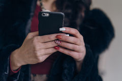 Elegant model in black coat with phone. Portrait of a seductive lady in an elegant coat royalty free stock photo