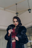 Elegant model in black coat with phone. Portrait of a seductive lady in an elegant coat stock image