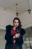Elegant model in black coat with phone. Portrait of a seductive lady in an elegant coat stock images