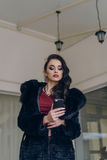 Elegant model in black coat with phone. Portrait of a seductive lady in an elegant coat royalty free stock images
