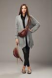 Elegant model in grijze geweven cardigan met twee pak van leerfanny royalty-vrije stock afbeelding