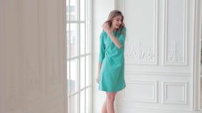 Elegant model posing near the window in mint color dress stock video