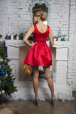 Elegant model in red party dress near commode royalty free stock image
